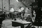 Black and white shot of Charlton sitting at desk in studio with ABC TV cameras around him and production staff in background.