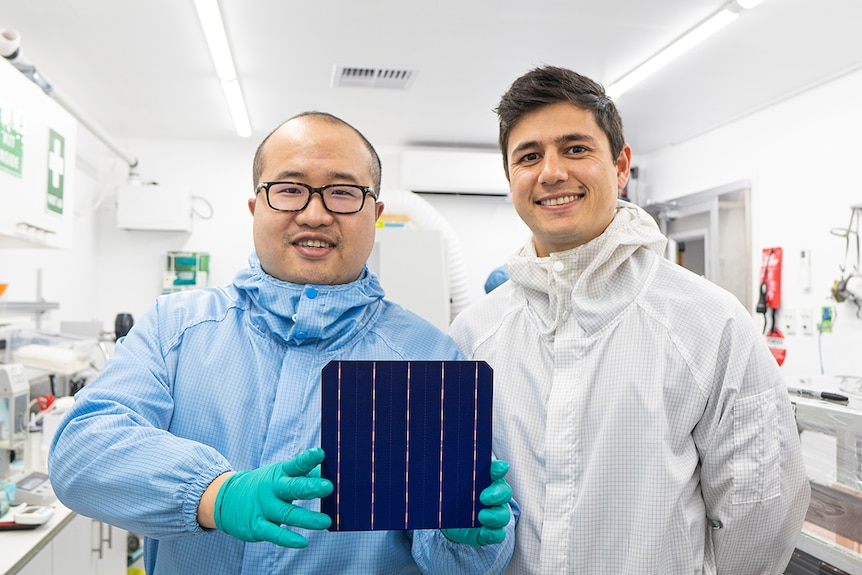 David Hu and Vince Allen wear protective suits and hold a solar cell.