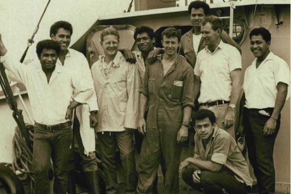 A black and white shot of nine men standing on a boat.