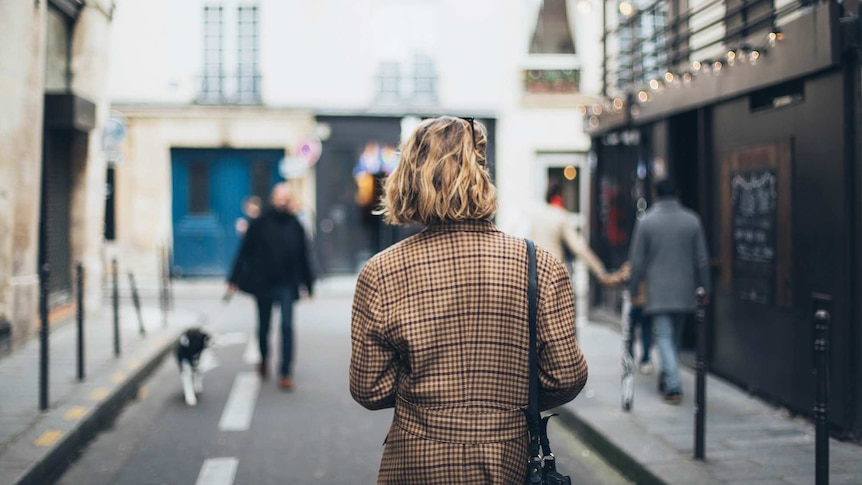 Photo of the back of a woman with short hair walking down a narrow street, with other people.