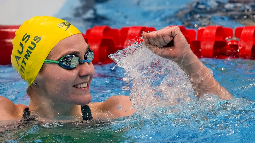 Ariarne Titmus at the end of the pool smiles while holding one fist in the air in celebration.