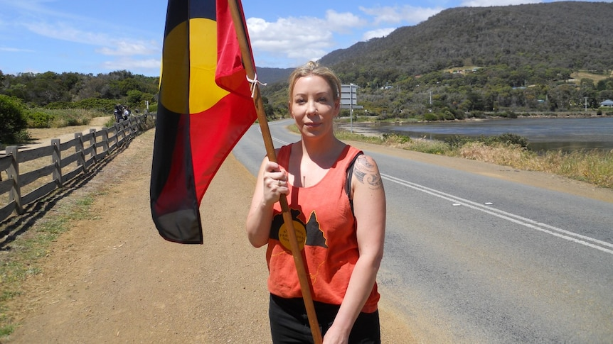 A young woman stands on the road holding an Aboriginal flag
