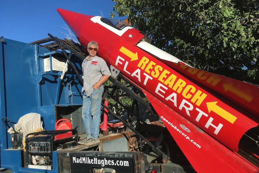 Mike Hughes stands in front of a large red rocket with Research Flat Earth written on the side