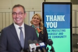 A sign saying thank you for being vaccinated stands behind a man and woman smiling