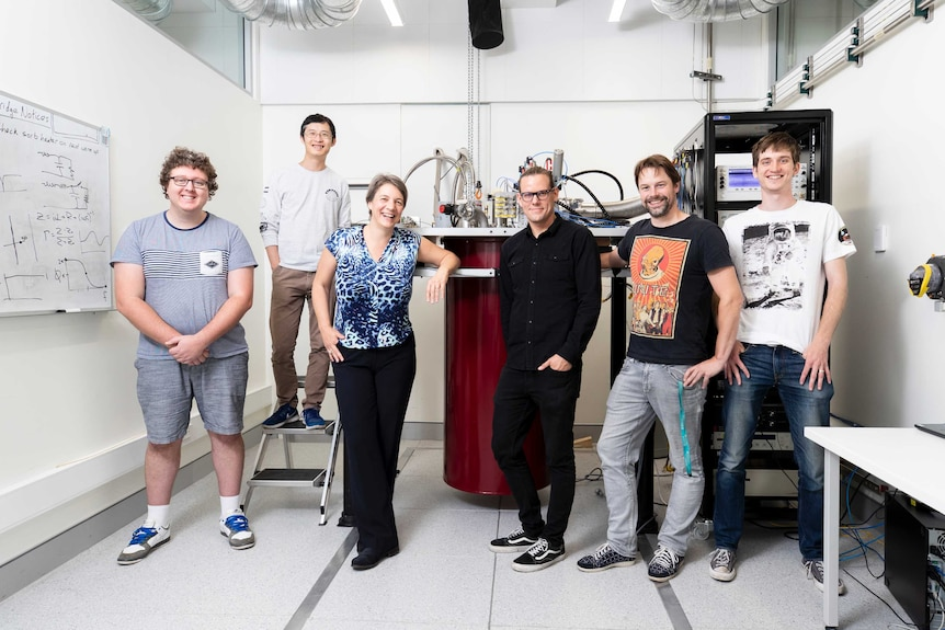 Six scientists stand casually and smile, with pipes and apparatus on a desk behind them.