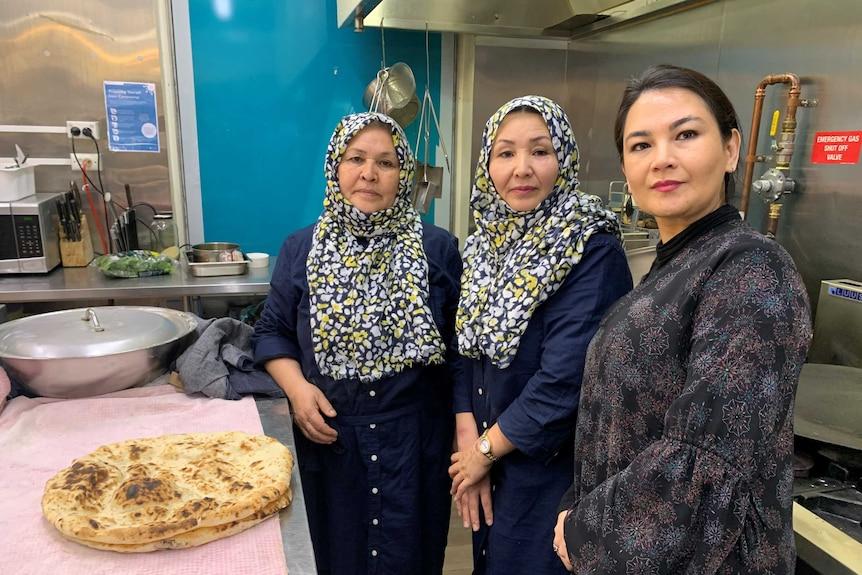 Three Afghan Hazara women, two hearing headscarfs in a commercial kitchen.