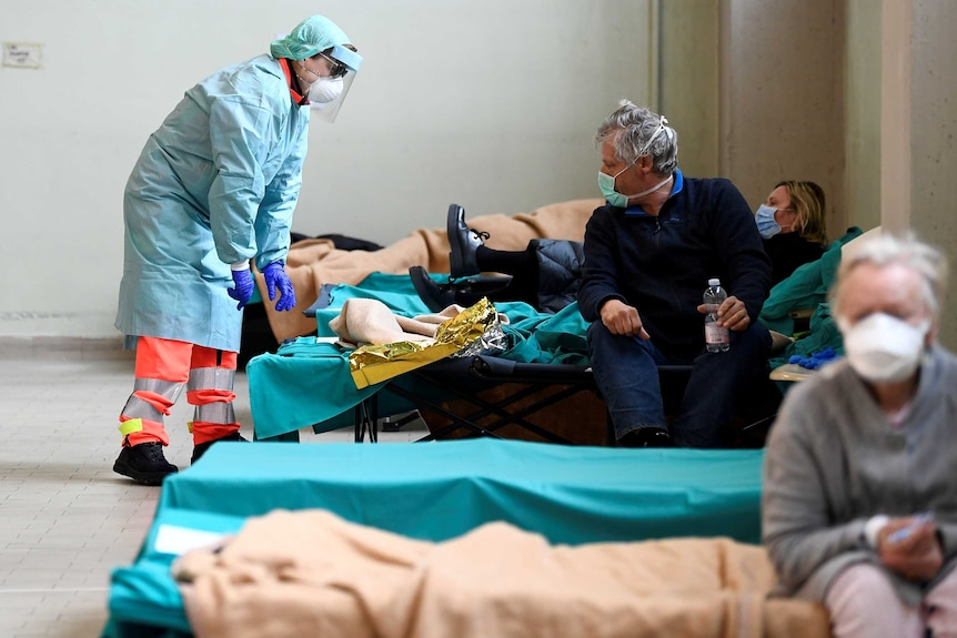 A female health worker in full hazmat gear leans over a man's bed