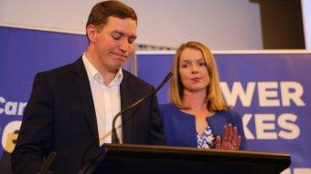 Alistair Coe frowns as his wife applauds.