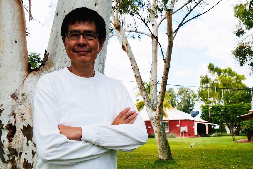 Man standing outside at a farm, in front of the homestead.