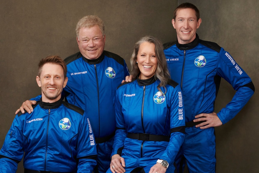William Shatner and three other members of Blue Origin's second human spaceflight pose for a photo in astronaut gear.