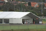 A large white tent for the drive-through testing site lies empty under grey skies.
