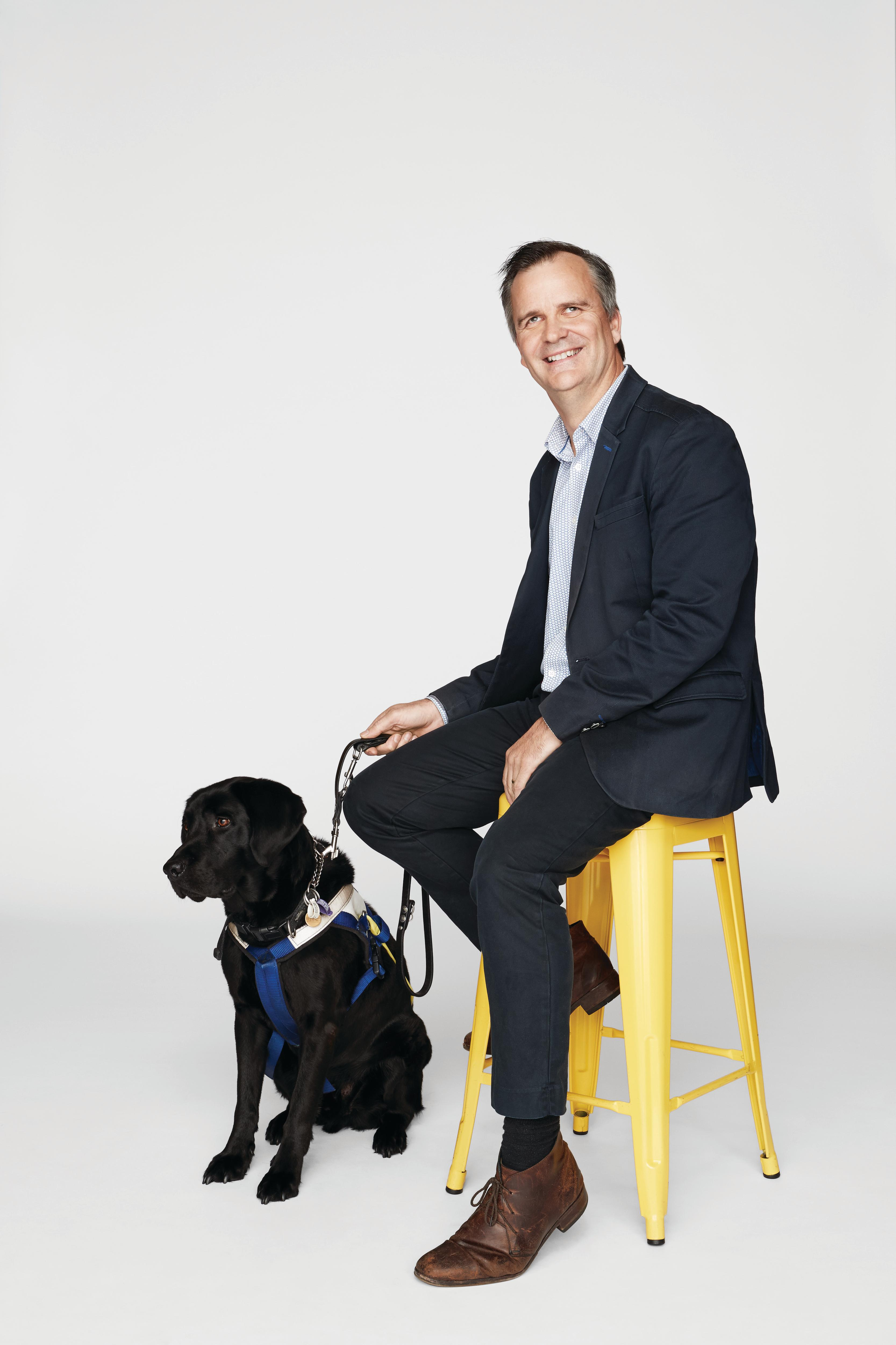 Chris Edwards sits on a stool while his Seeing Eye Dog, Odie, rests at his feet.