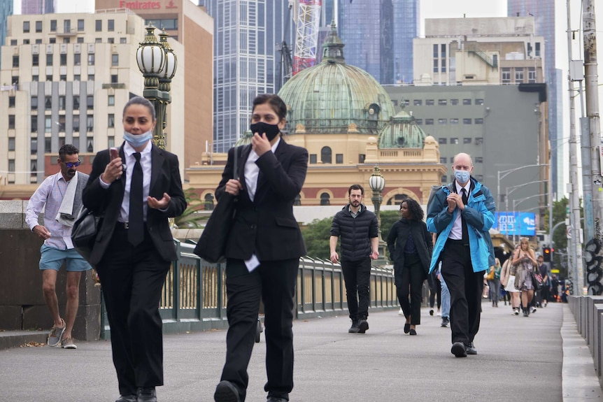 People walk across the bridge over the Yarra with Flinders Street Station in the background.