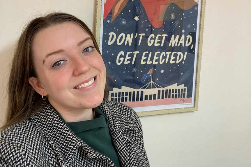 """A young woman standing in front of an election poster that says """"don't get mad, get elected"""""""