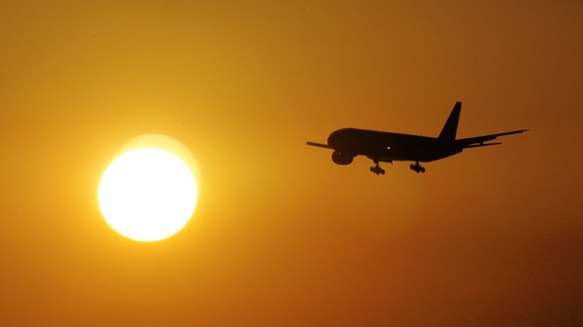 A plane flying into the sun as it is setting.