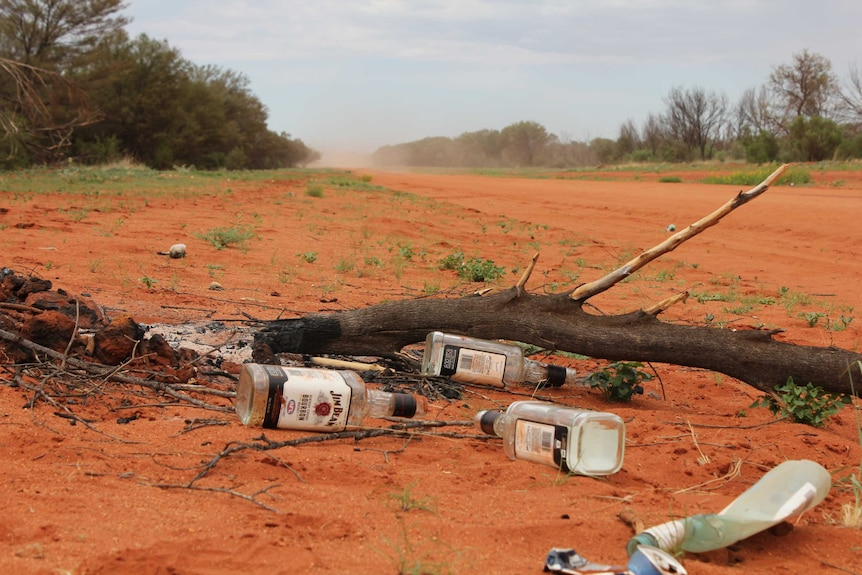Empty bottles of spirits on a red dirt road.