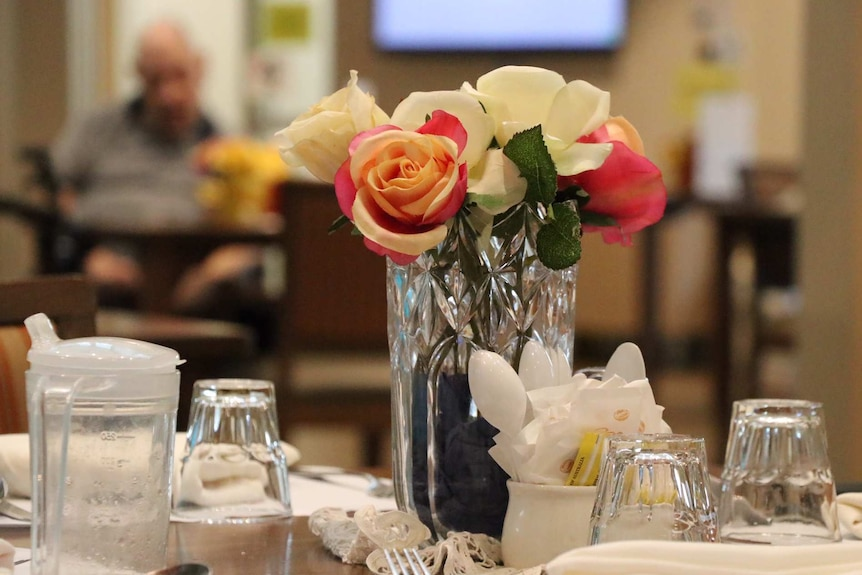 Dining table at a nursing home with an anonymous elderly man in the background.