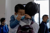 A child being held by a woman cries as he waits in line to board a plane.