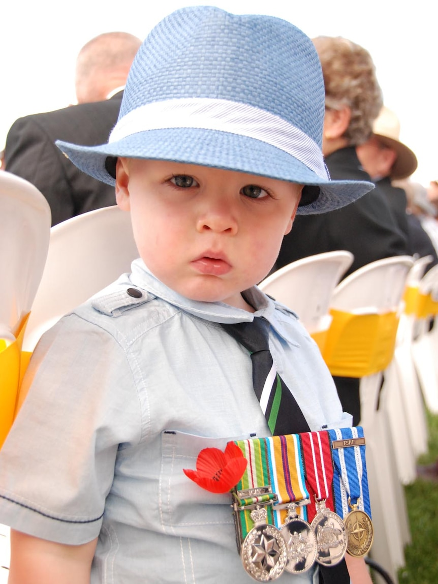 Ziggy Till wears his father's medals at the Remembrance Day service in Canberra.