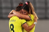 Two Australian female rugby sevens players embrace as they console each other after losing to Fiji.