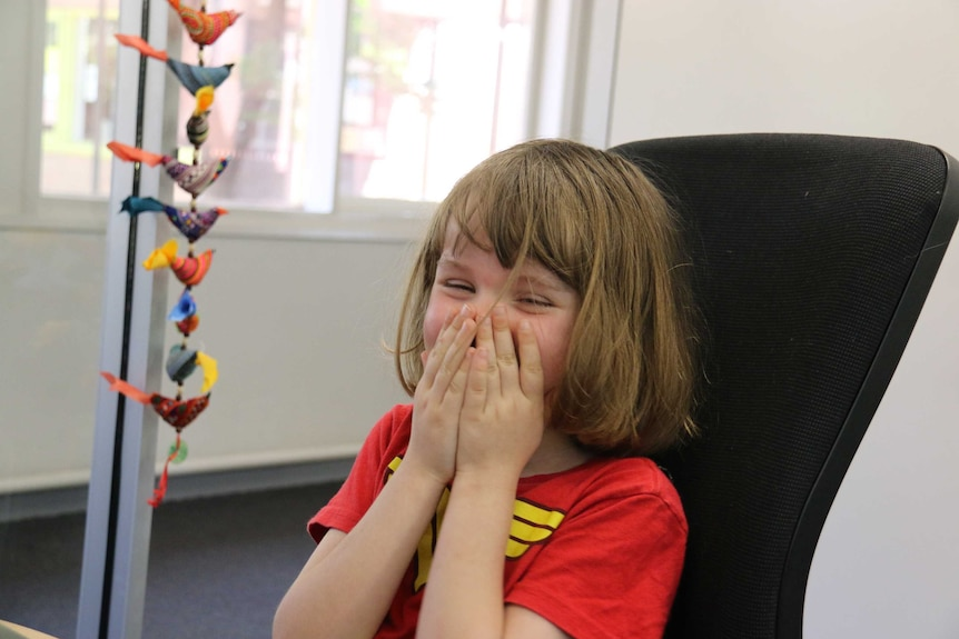 A laughing girl puts her hands to her mouth.