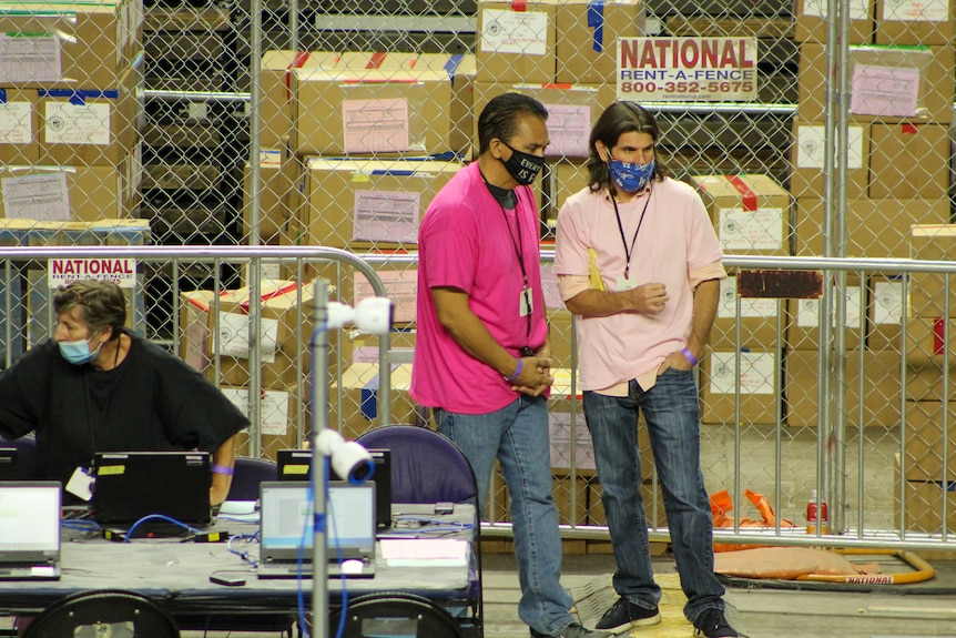 Two men in pink shirts and COVID masks observe people counting election ballots