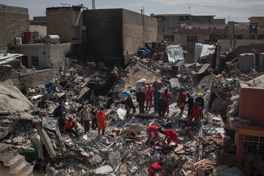 Civil protection rescue teams search through the debris of a house destroyed in a March 17 US airstrike in Mosul.