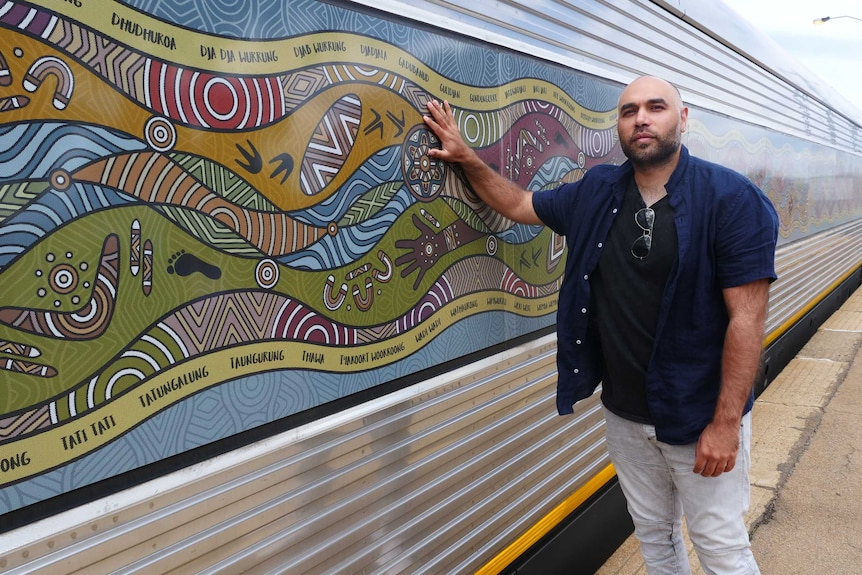 A man stands in front of train with an Indigenous design on the windows.
