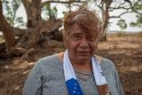 Regina McKenzie standing in front of sprawling gum trees