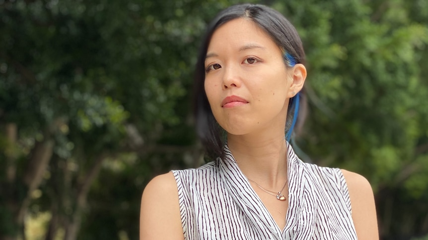 An Asian woman wearing a black and white sleeveless blouse stands in front of trees.