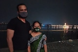 A man in a black tshirt and mask stands with his arm around an older woman in a sari and mask. A city and river in the backgroun