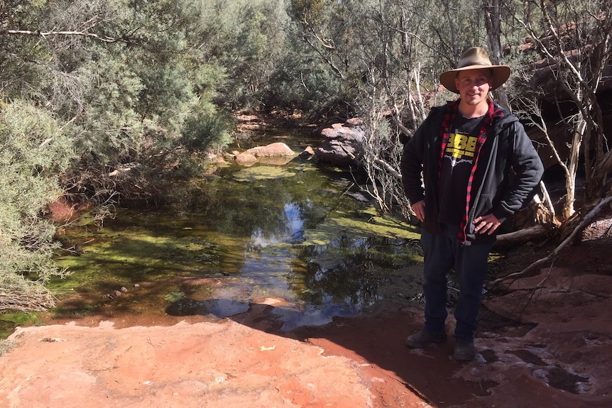 A man wearing a hat stands with his hands on his hips near a waterhole