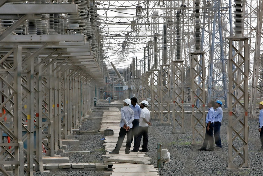 Engineers inspect electric transmission lines at Adani's thermal plant in the state of Gujarat.