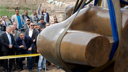 Onlookers watch as the torso of an ancient Egyptian pharaoh statue is excavated in a Cairo suburb.