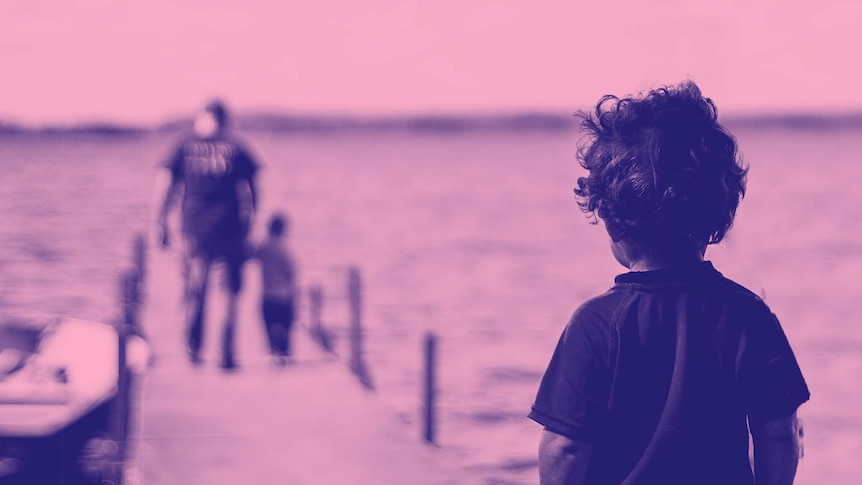 Young boy looks on at a father and a child on a jetty for a story about the effects of not being shown kindness when young.