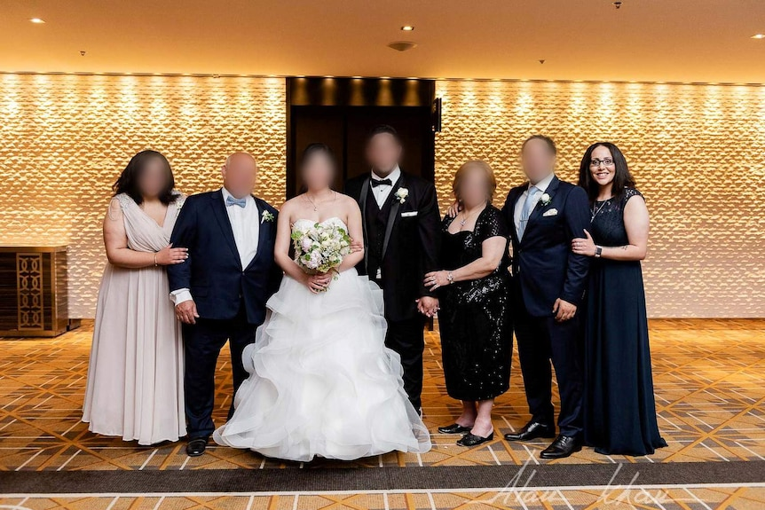 Abdelmalek poses in a gown as part of a formal family wedding photo.