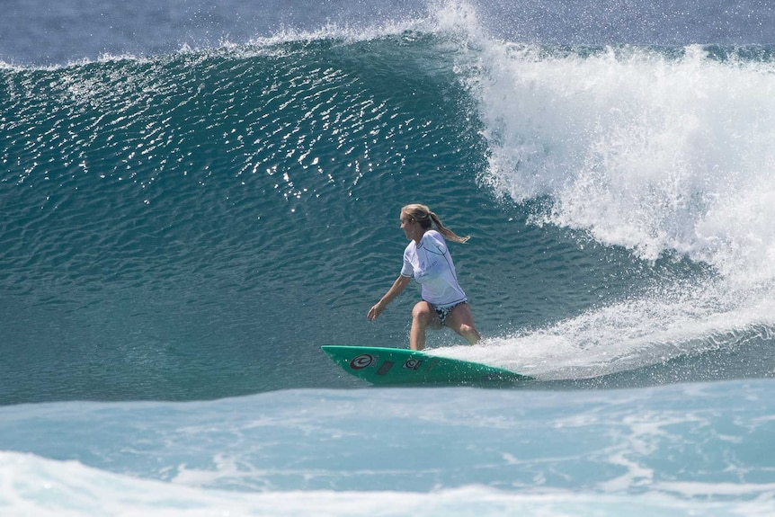 A woman with one arms surfs a large wave.