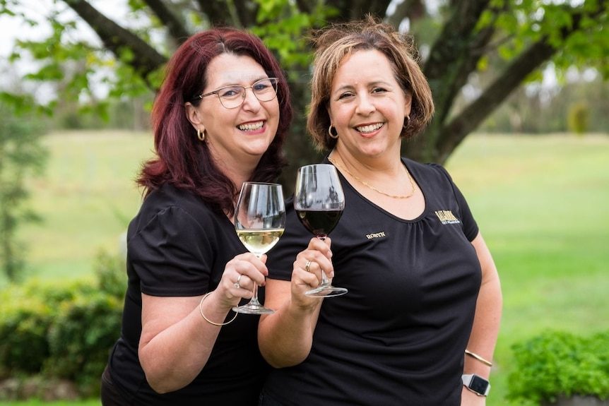 Leanne and Robyn clink wine glasses.