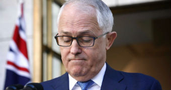 Malcolm Turnbull frowns, with his eyes cast downward, at a press conference in a courtyard
