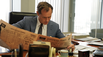 Jude Law in an 80s suit looking at a newspaper stressed in the film The Nest