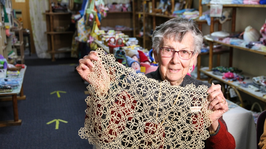 A woman holds an original piece of lace tatting.