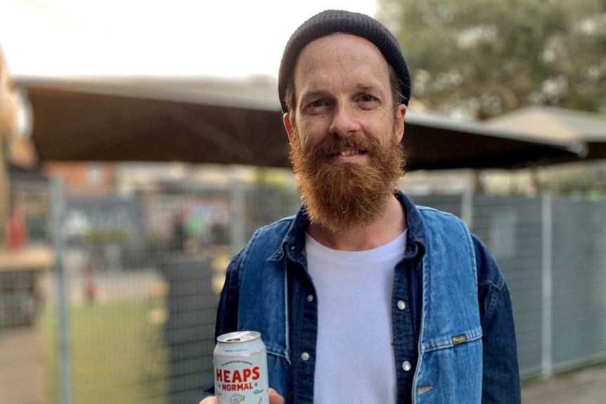 A man in a beanie holds onto a can of non-alcoholic beer.