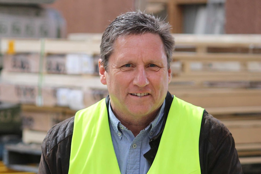 Ralph Doedens stands in a warehouse wearing a high visibility vest.