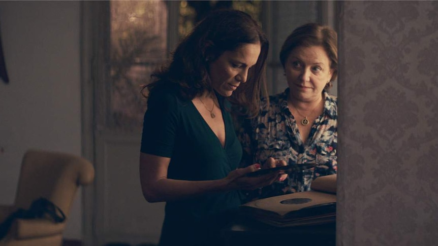 A 40-ish woman and a 60-ish woman in a living room, looking at a record as they stand close together.