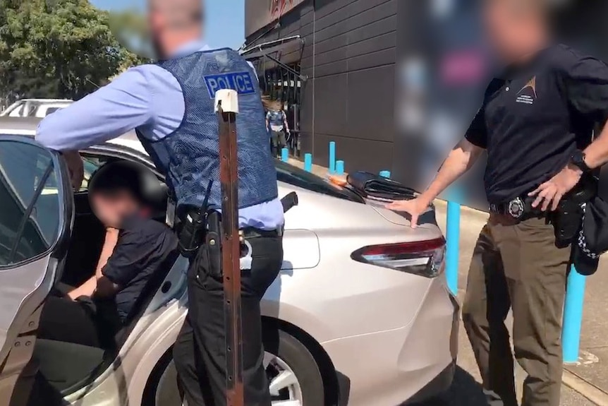 Two police who have their identities blurred look at an arrested man in the back of an unmarked police car