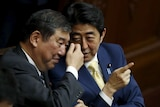 Japan's Prime Minister Shinzo Abe (R) talks with minister in charge of reviving local economies Shigeru Ishiba during the plenary session of the parliament in Tokyo July 16, 2015.