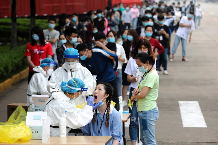 Workers line up for medical workers to take swabs for the coronavirus test at a large factory in Wuhan.