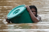 A woman uses a plastic container as a floater while negotiating rising floodwaters