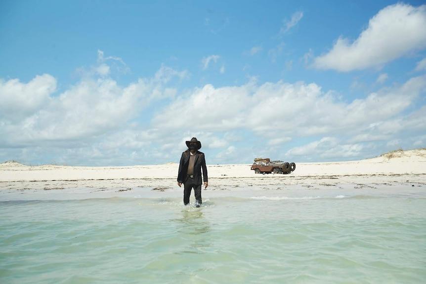 Warwick Thornton walks into the ocean fully dressed in The Beach documentary.