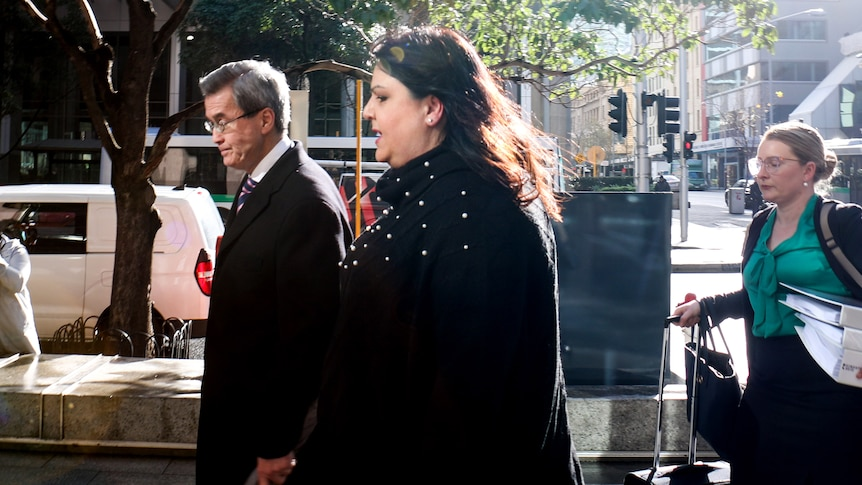 Ms Fewster walks into the building, flanked by a man and woman wearing formal clothes.
